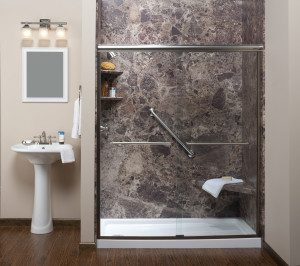 View of a neutral tone bathroom, featuring a glass-enclosed accessible shower with stone walls