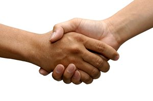 Two hands enclosed in a handshake gesture