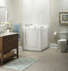 View of a cream toned bathroom, featuring a walk-in tub installed into a corner of the room