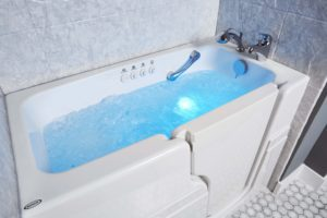 View of a Jacuzzi walk-in tub with blue chromotherapy lights filled with water