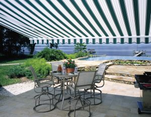 Retractable awning casting a shadow over a patio dining area overlooking a lake