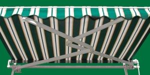 View of metal arms underneath of a green striped retractable awning