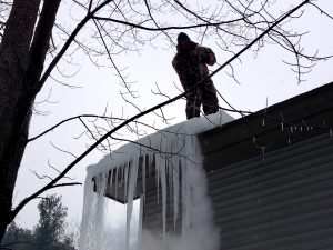 A Rainbow Seamless Employee Removing an Ice Dam