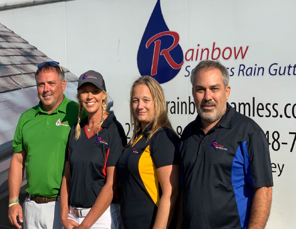 Rainbow Seamless System owners, Matt and Mike, posing for a photo with Jen and Jen in front of their work trailer