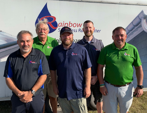 Rainbow Seamless Systems sales consultants, Mike, Dave, Billy, Cory, and Matt, posing for a photo in front of their work trailer