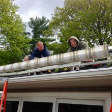 Rainbow Seamless Employees installing a motorized awning